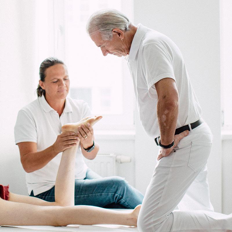 Dr. Altenhuber und eine Physiotherapeutin bei der Behandlung einer Achsfehlstellung einer jugendlichen Patientin
